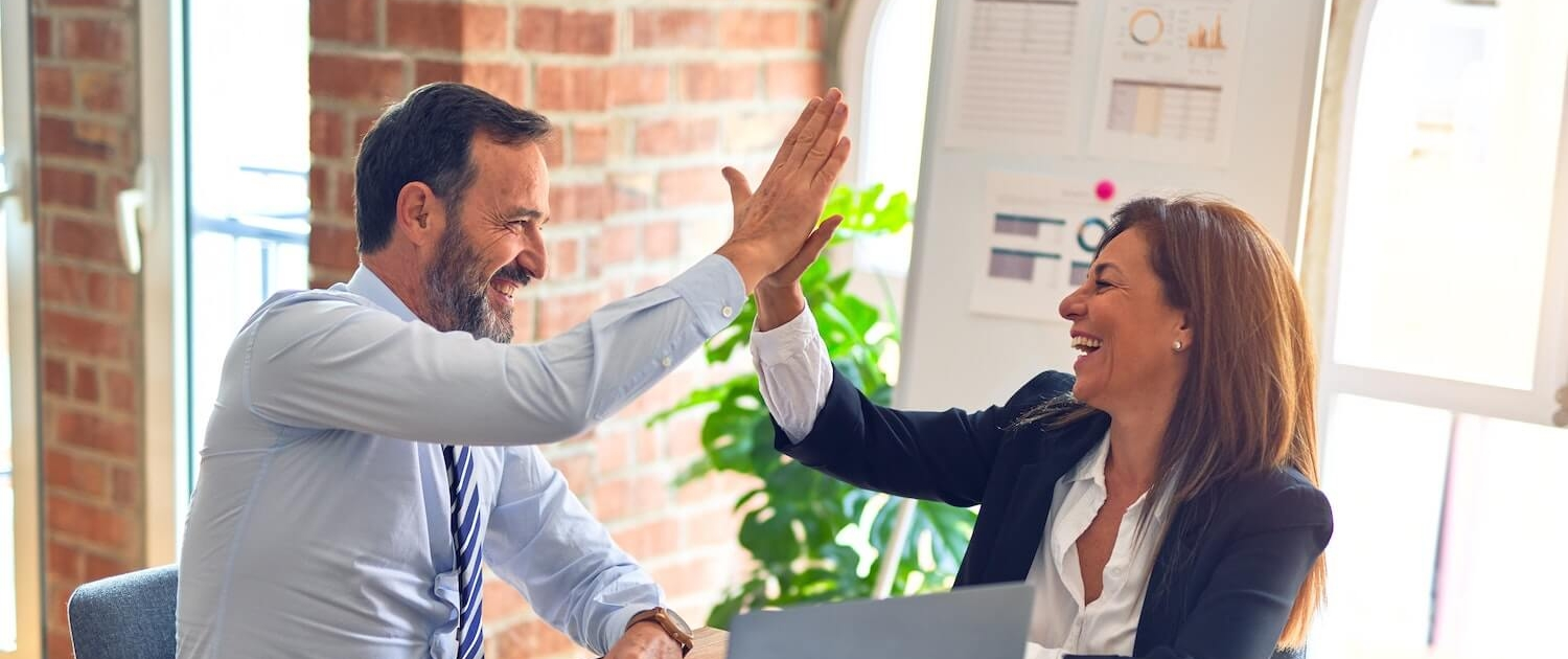 happy business owners with marketing success doing a high five
